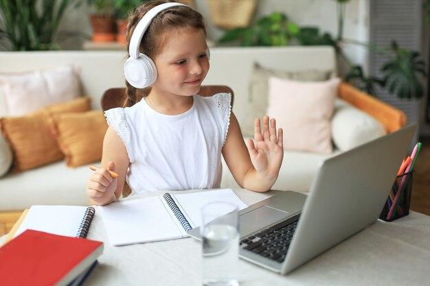 ビデオコールの先生とオンラインで勉強している少女。 covid-19コロナウイルスの流行における遠隔教育。