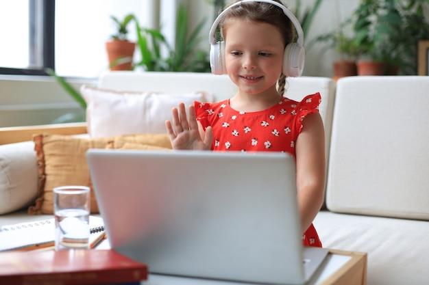 ビデオコールの先生とオンラインで勉強している少女。通信教育。