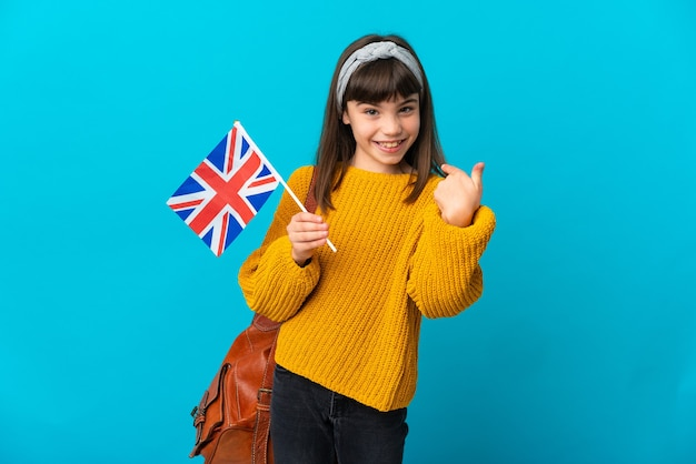 Little girl studying english isolated on blue background giving a thumbs up gesture