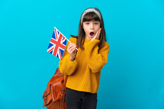 Little girl studying english isolated on blue background with surprise and shocked facial expression