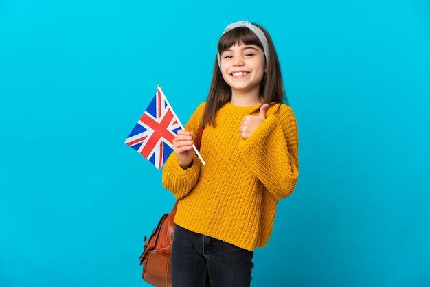 Маленькая девочка, изучающая английский язык, изолирована на синем фоне, показывая большой палец вверх