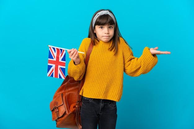 Маленькая девочка, изучающая английский язык, изолированная на синем фоне, сомневается, поднимая руки
