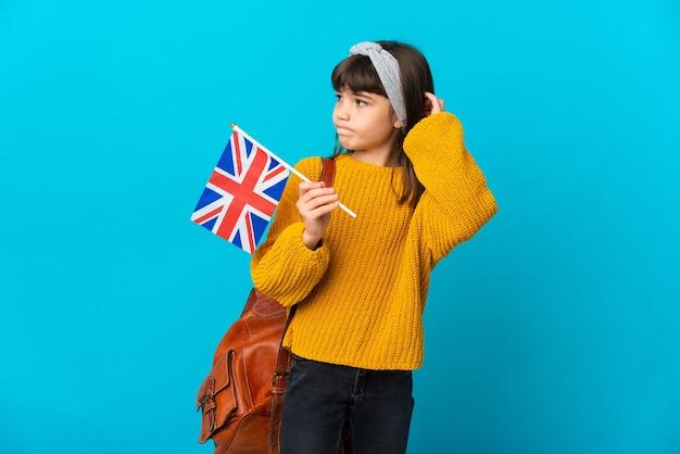 Маленькая девочка изучает английский язык, изолированные на синем фоне, сомневаясь