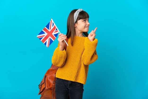 좋은 아이디어를 가리키는 파란색 배경에 고립 된 영어를 공부하는 어린 소녀