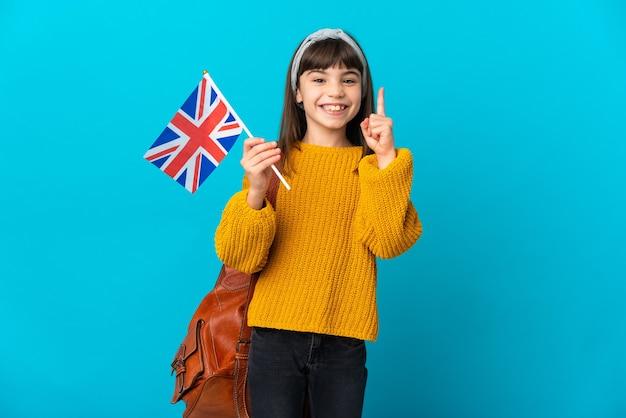 Маленькая девочка, изучающая английский язык, изолирована на синем фоне, указывая на отличную идею