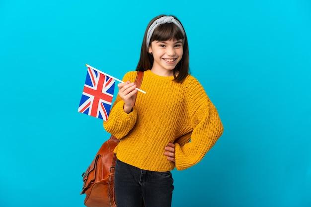腰に腕と笑顔でポーズをとって青い背景に分離された英語を勉強している少女