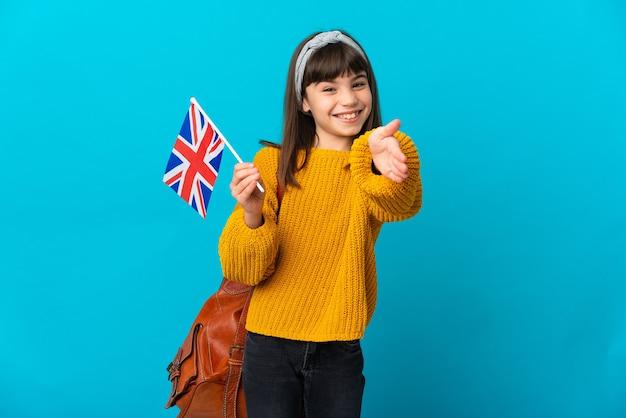 Маленькая девочка, изучающая английский язык, изолирована на синем фоне, пожимая руку для заключения хорошей сделки