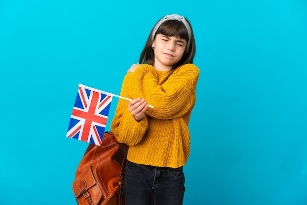 Маленькая девочка, изучающая английский язык, изолирована на синем фоне и страдает от боли в плече из-за того, что приложила усилия