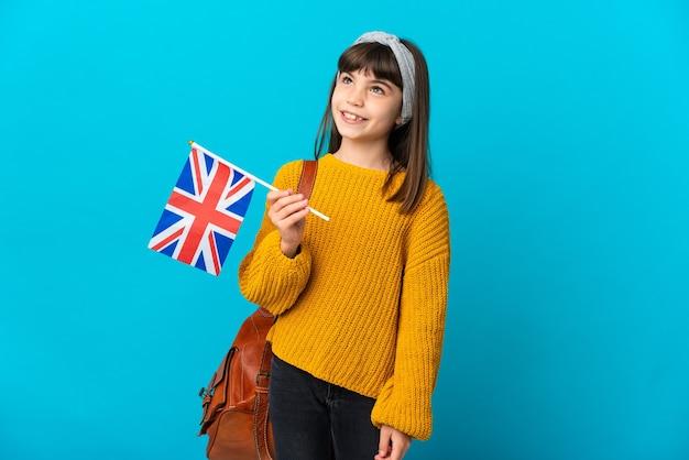 찾는 동안 아이디어를 생각하는 파란색 배경에 고립 된 영어를 공부하는 어린 소녀