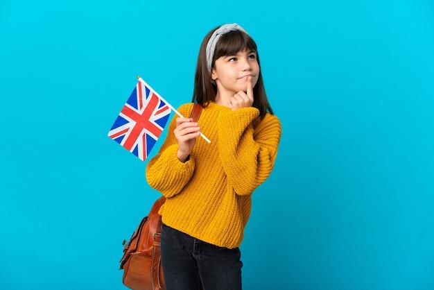 찾는 동안 의심을 갖는 파란색 벽에 고립 된 영어를 공부하는 어린 소녀