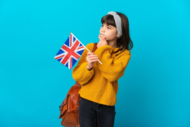 Маленькая девочка, изучающая английский язык, изолирована на синей стене, сомневаясь