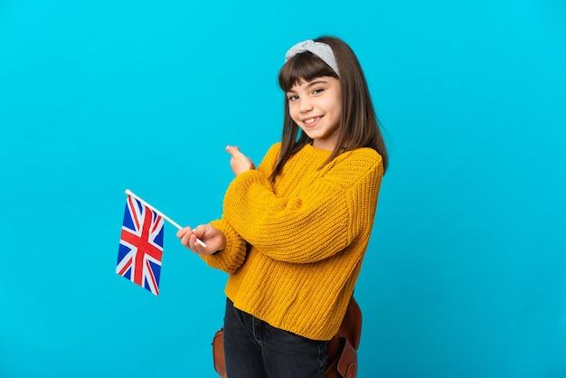 Маленькая девочка, изучающая английский язык, изолирована на синей стене, указывая назад