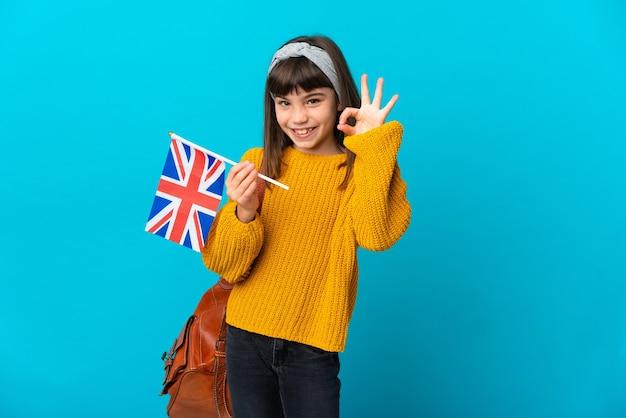Маленькая девочка, изучающая английский язык, изолирована на синей стене, показывая пальцами знак ок