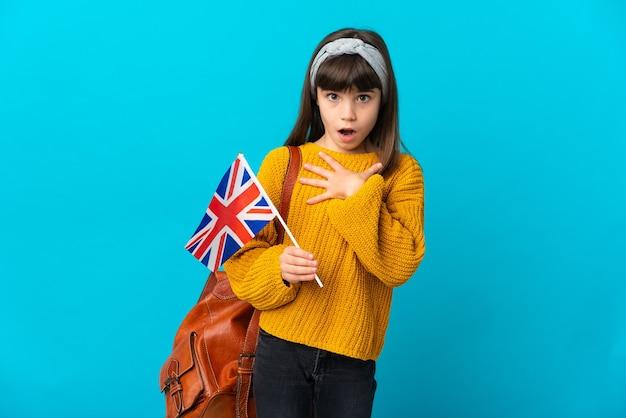 Маленькая девочка, изучающая английский язык, изолированная на синей стене, удивлена и шокирована, глядя вправо