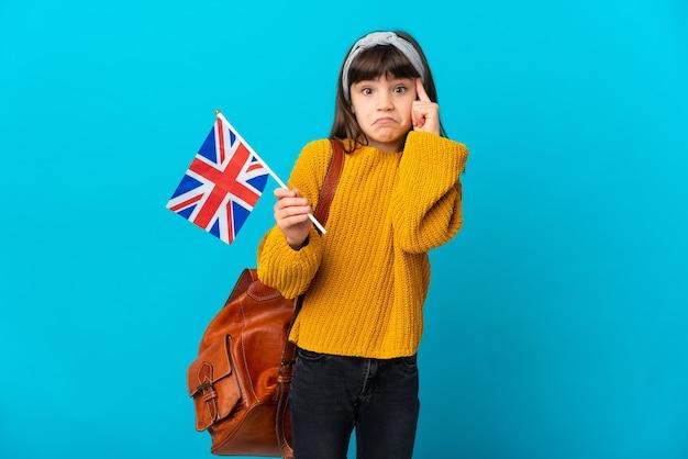 Маленькая девочка, изучающая английский язык, изолирована на синей стене, думая об идее