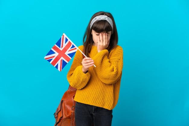 Маленькая девочка, изучающая английский язык, изолирована на синей стене с усталым и больным выражением лица