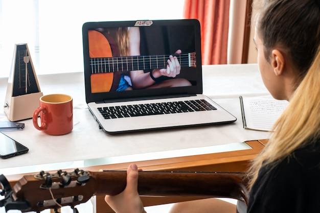 Маленькая девочка изучает уроки игры на гитаре дома