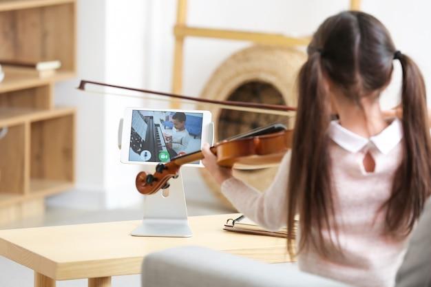 自宅でオンラインで友達と音楽を勉強している少女