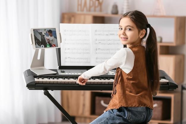집에서 온라인으로 그녀의 친구와 함께 음악을 공부하는 어린 소녀