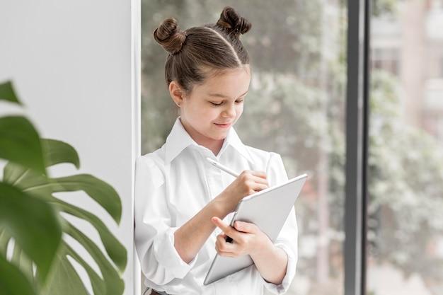 Маленькая девочка учится на своем планшете