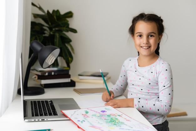 Маленькая девочка учится онлайн, используя свой ноутбук дома