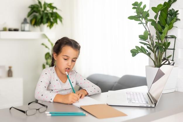 집에서 노트북을 사용하여 온라인으로 공부하는 어린 소녀