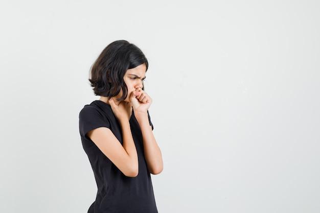 Маленькая девочка страдает от кашля в черной футболке и выглядит больной. передний план.