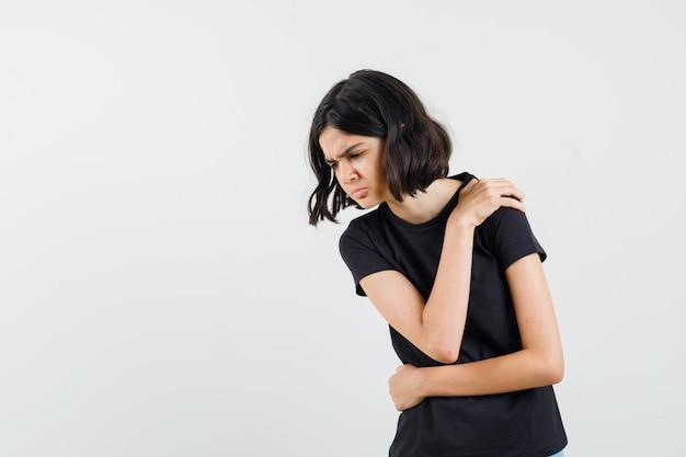 Маленькая девочка страдает от боли в плече в черной футболке и выглядит усталой, вид спереди.