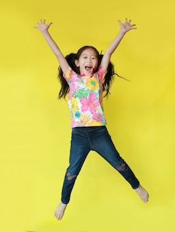 Little girl in summer t-shirt jumping on air
