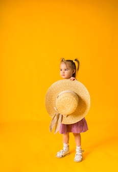 A little girl in a sundress holding a straw hat on a yellow surface with space for text