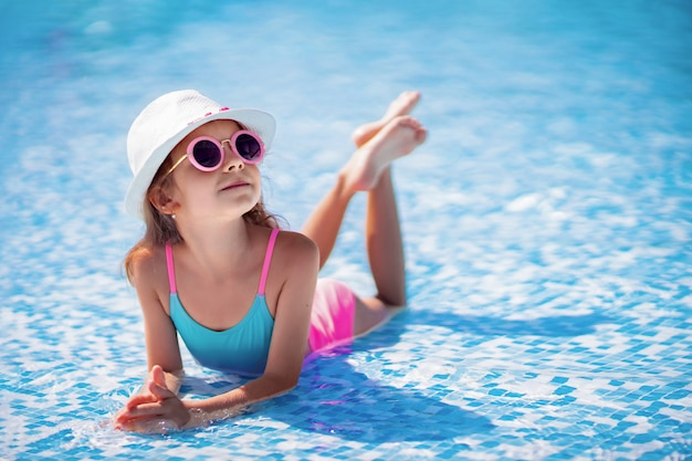 Little girl in sunglasses and hat with unicorn in outdoor swimming pool of luxury resort on summer vacation on tropical beach island