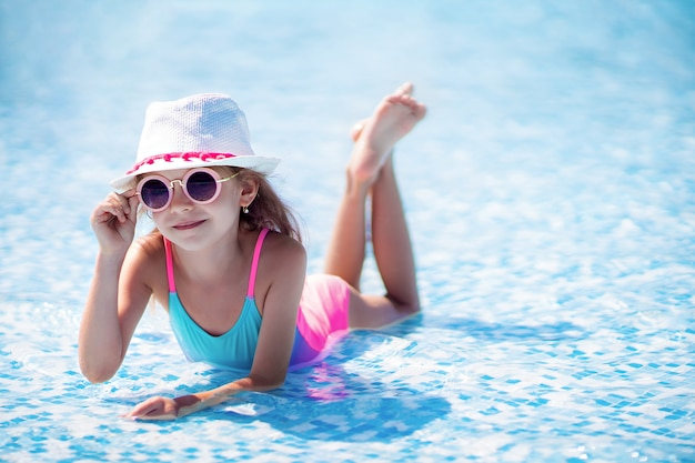 Little girl in sunglasses and hat with unicorn in outdoor swimming pool of luxury resort