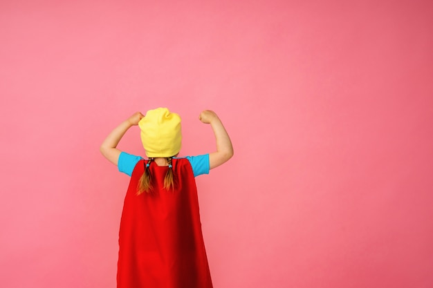Little girl in a superhero costume in red cape and hat shows how strong she is.