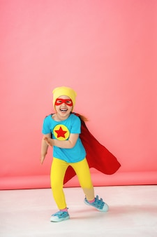 A little girl in a superhero costume, running forward on a pink