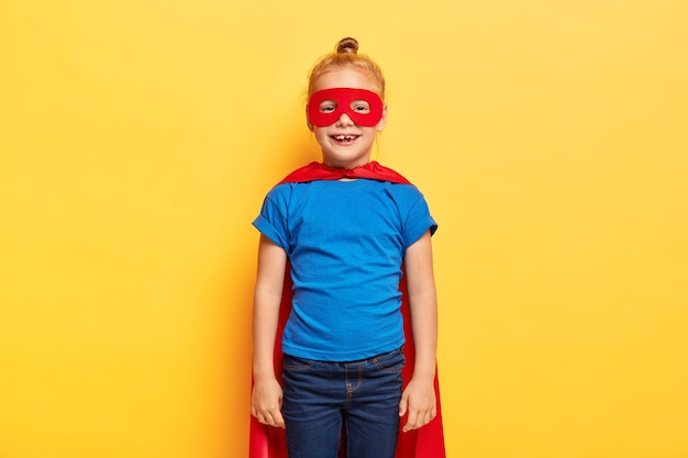 Little girl superheroine wears special suit with red cape