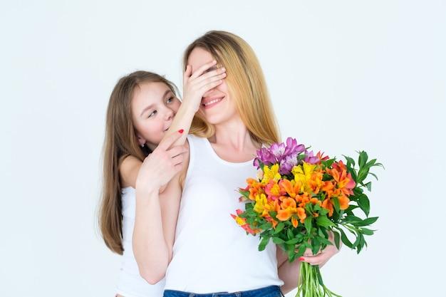 アルストロエメリアの花の束で彼女のお母さんを驚かせる少女