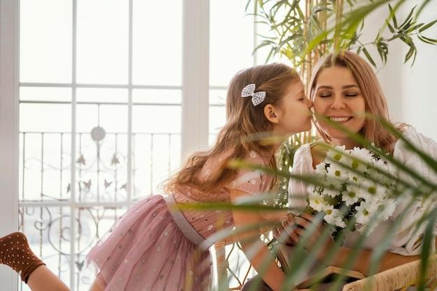 春の花の花束で母親を驚かせる少女