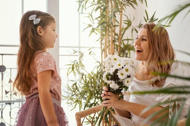 Little girl surprising mom with a bouquet of delicate spring flowers