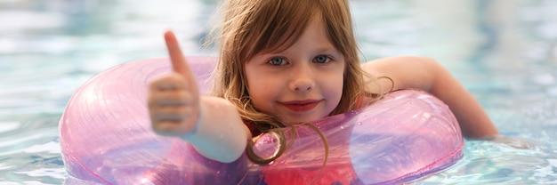 풍선 원을 사용하여 수영장에서 수영하고 엄지손가락을 보여주는 어린 소녀