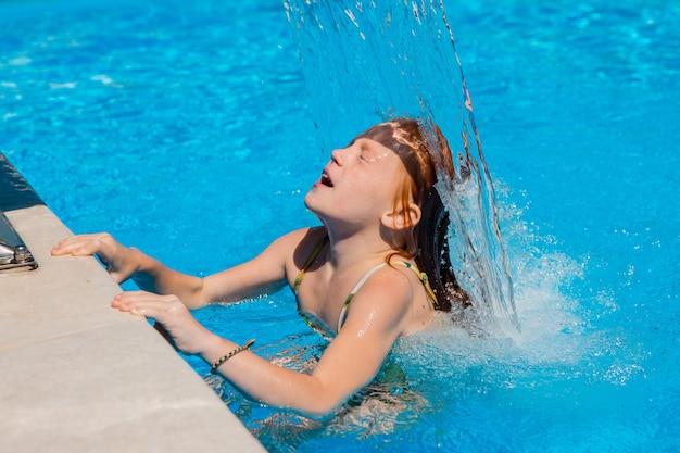 Маленькая девочка плавает в бассейне летом
