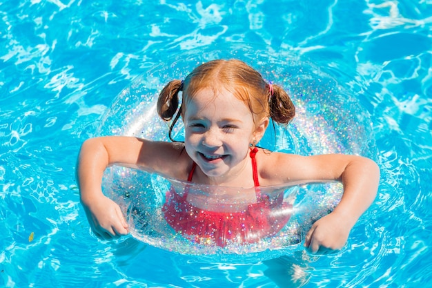 Little girl swimming in the pool in summer