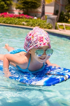 Little girl swimming on a surfboard in swimmingpoll