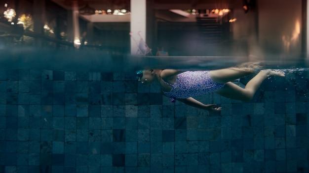 Маленькая девочка плавает в бассейне. фото высокого качества