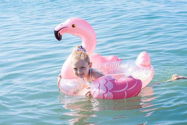 Little girl swims with a circle in the shape of a flamingo on the sea