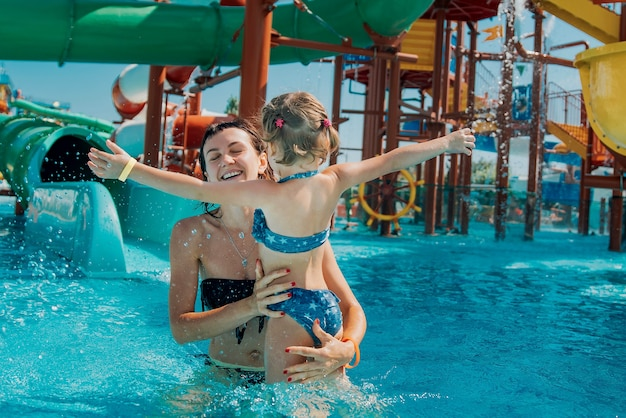Little girl in swimsuit girl hugs joyful mom in the water park pool mother and daughter play and swim in the outdoor pool