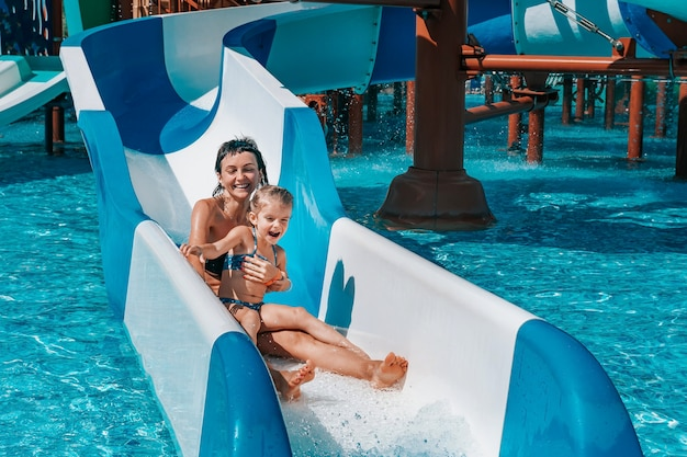 Little girl in swimsuit goes down the blue slides to the pool mom and daughter play and swim in the outdoor pool
