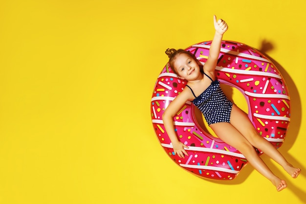 A little girl in a swimsuit is lying on an inflatable circle.