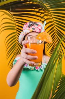 Little girl in swimsuit offering orange juice on yellow background.