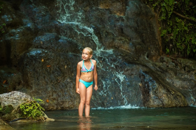 A little girl in a swimsuit at a waterfall in the jungle. nature trip near a beautiful waterfall, turkey