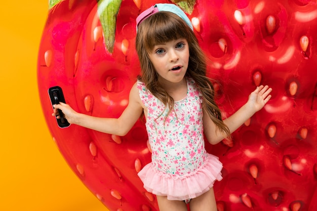 Little girl in a swimsuit with an air mattress in the form of strawberries